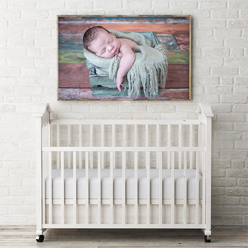 a photo of a large image hanging above a crib in a nursery featuring a newborn baby boy in a wooden crate