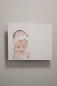 a photo of a metal print featuring a newborn girl