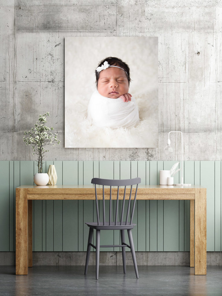 a newborn photo hanging over a desk