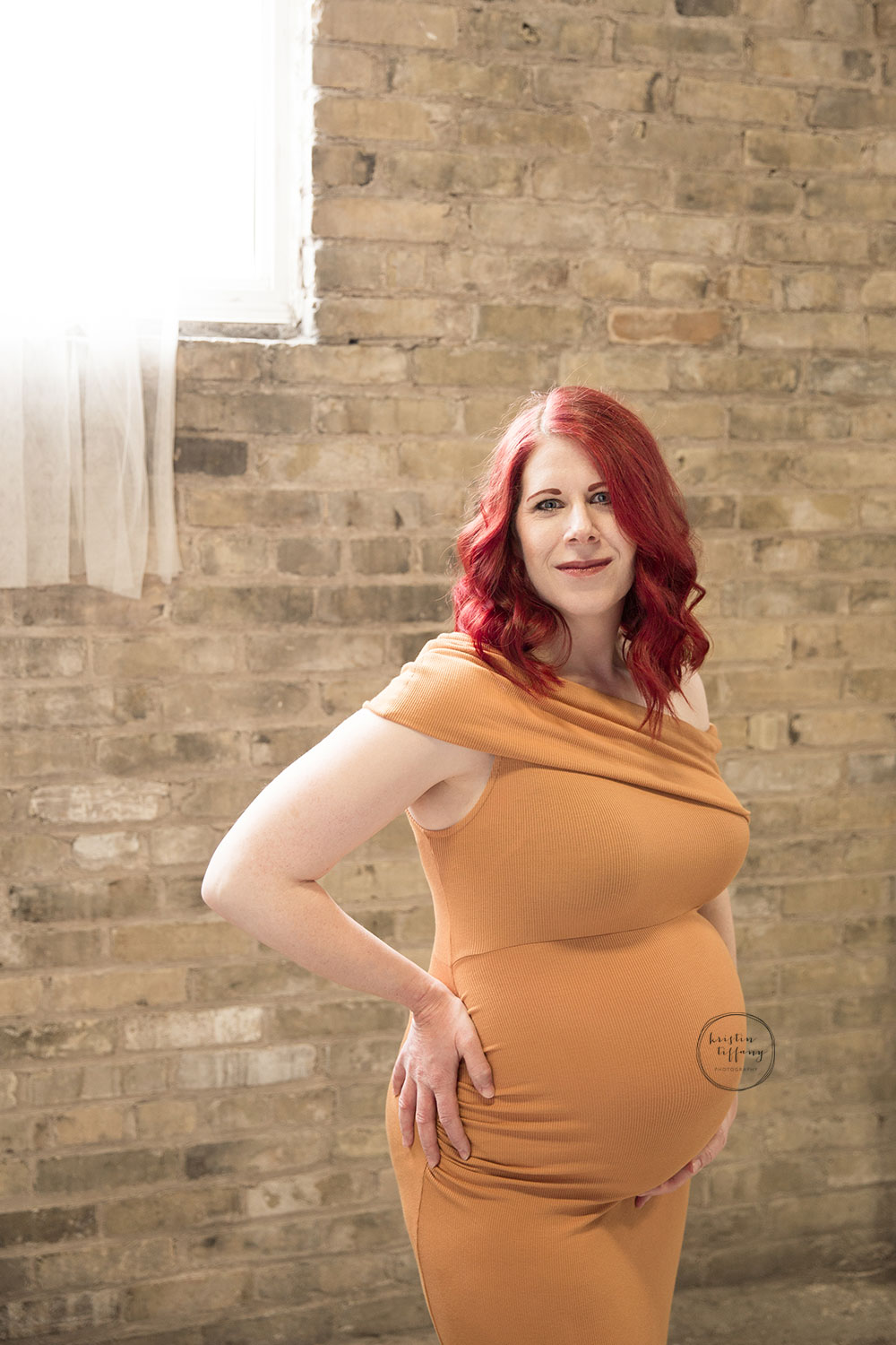 a maternity photo of a woman in a yellow dress with red hair