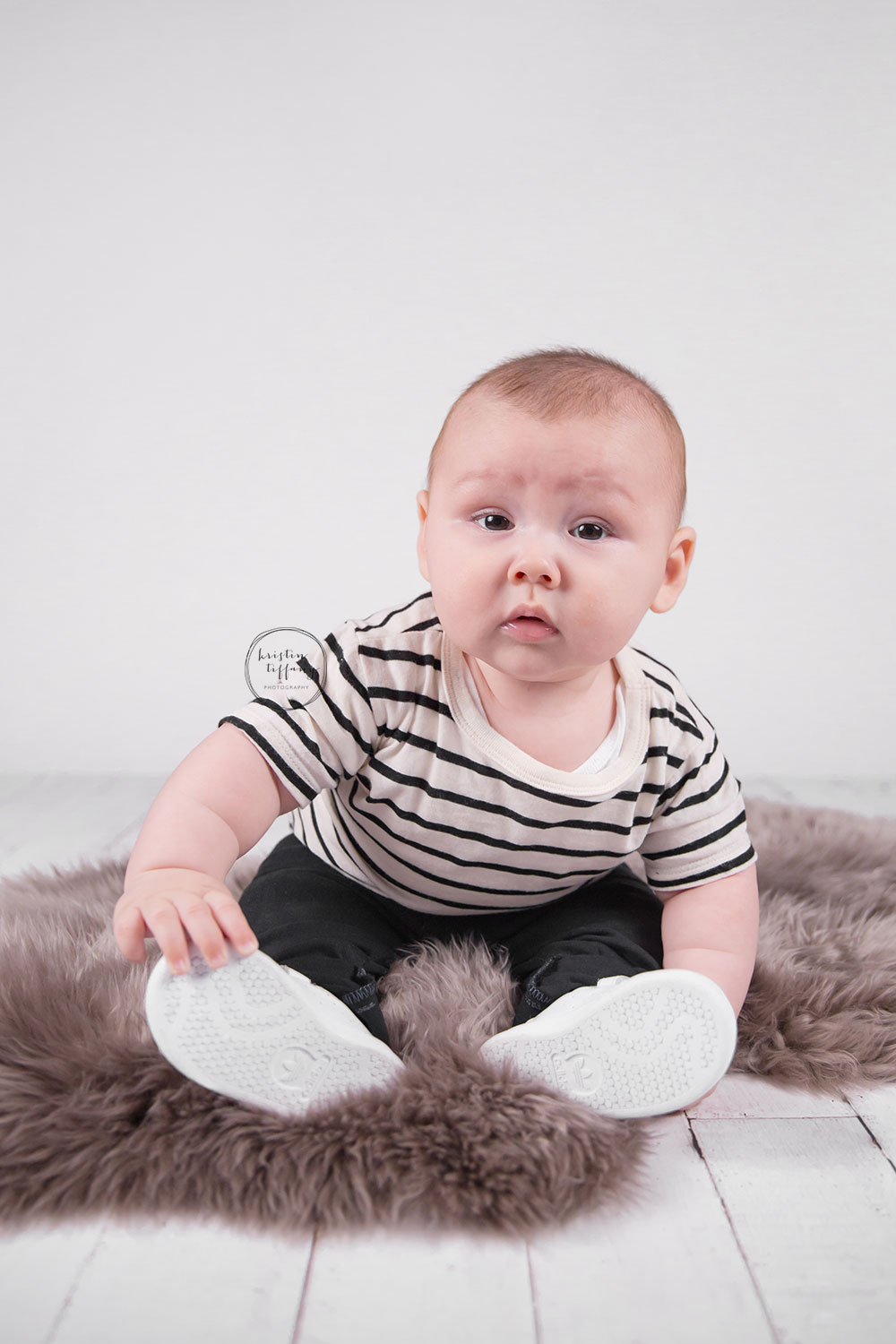 a photo of a baby boy on a fur rug