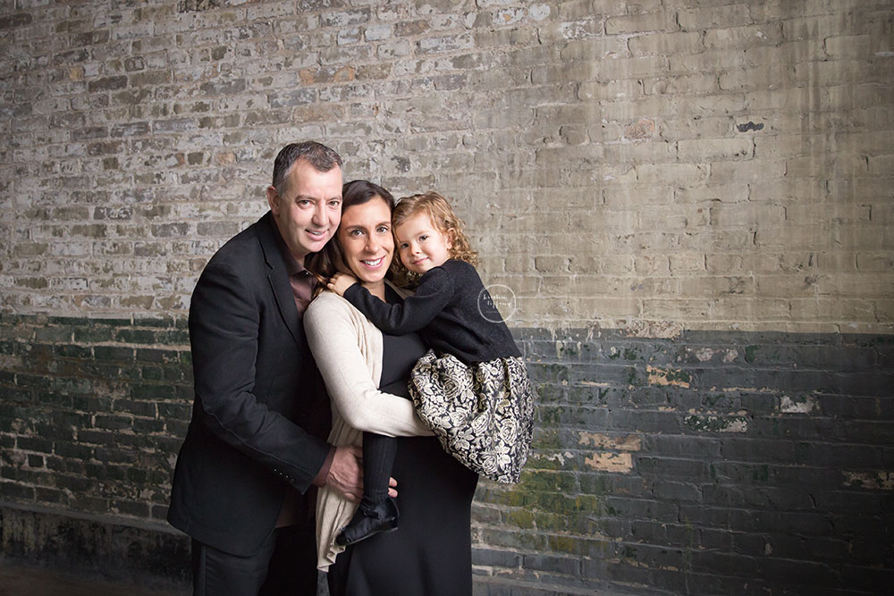 a family maternity photo by a distressed brick wall