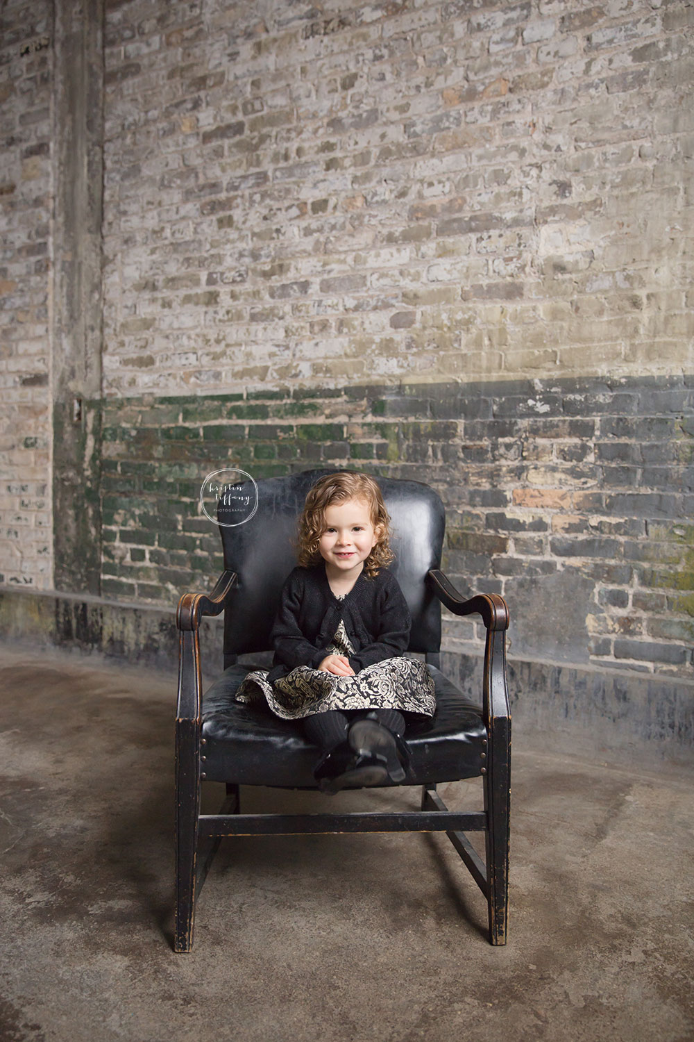 a photo of a little girl in a leather chair