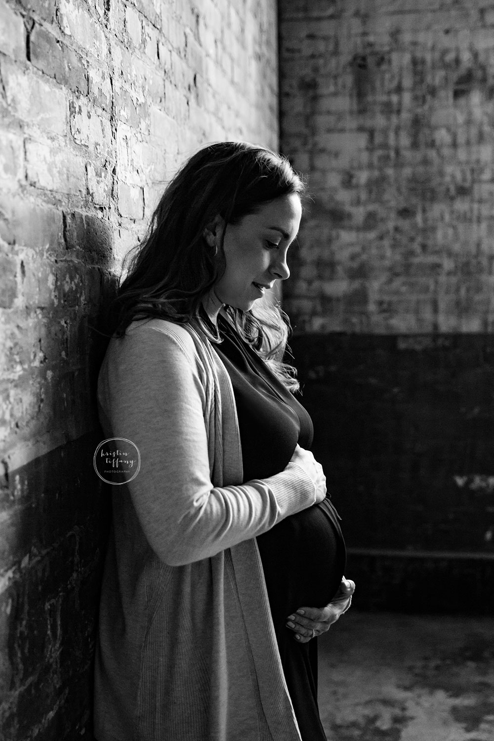 a maternity of a mother holding her belly by a brick wall