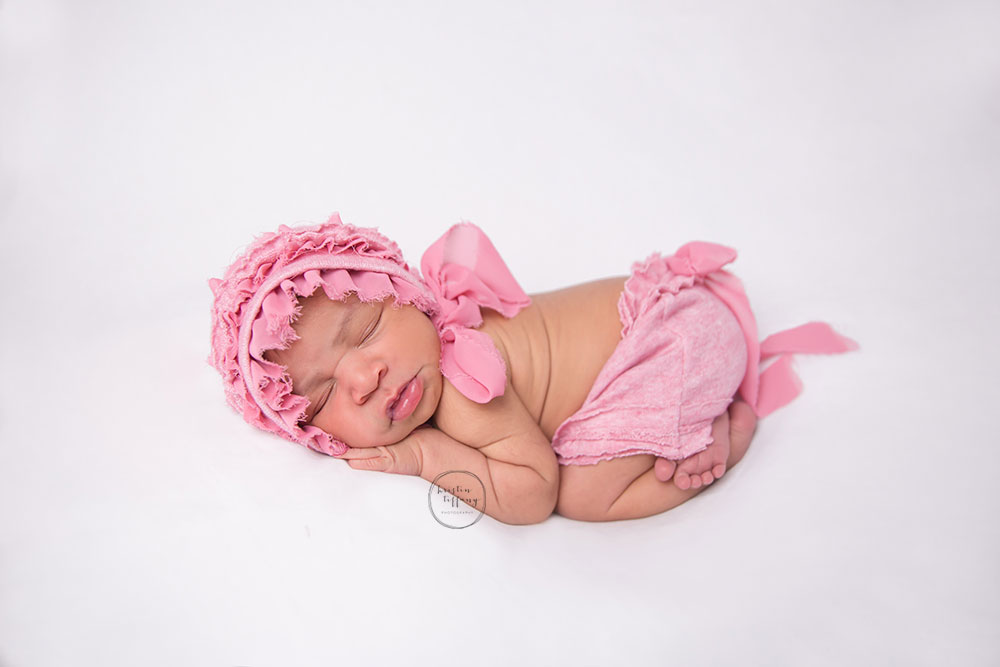 a newborn photo of a baby girl in a pink outfit