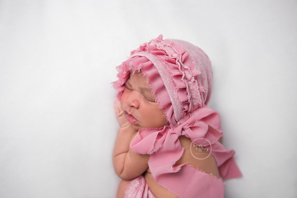 a newborn photo of a baby girl in a pink bonnet
