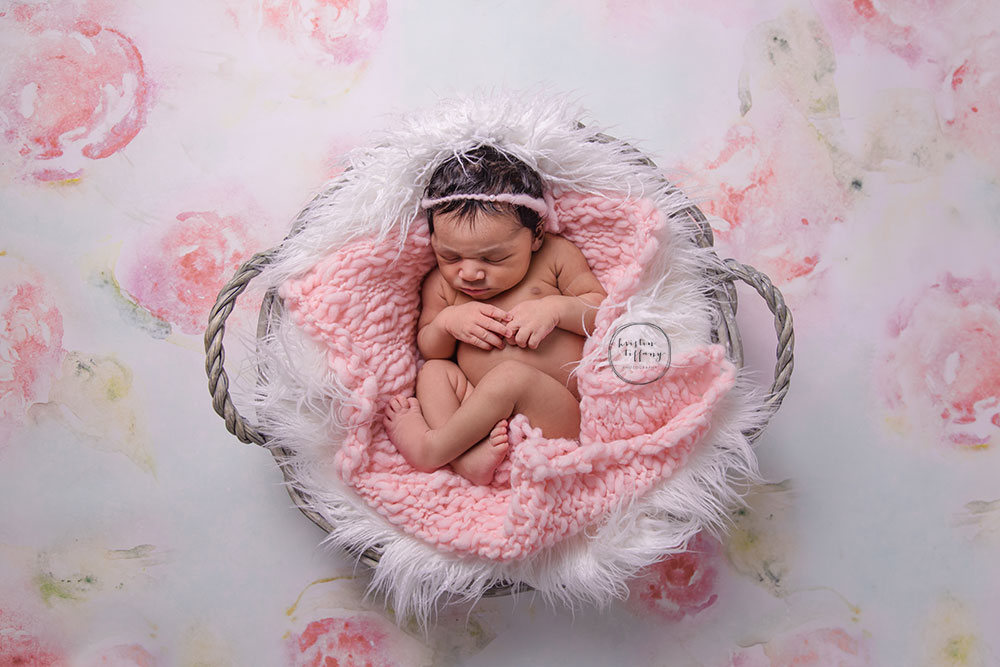 a newborn photo of a baby girl sleeping in a basket