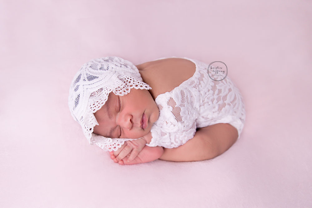 a newborn photo of a baby girl in taco pose