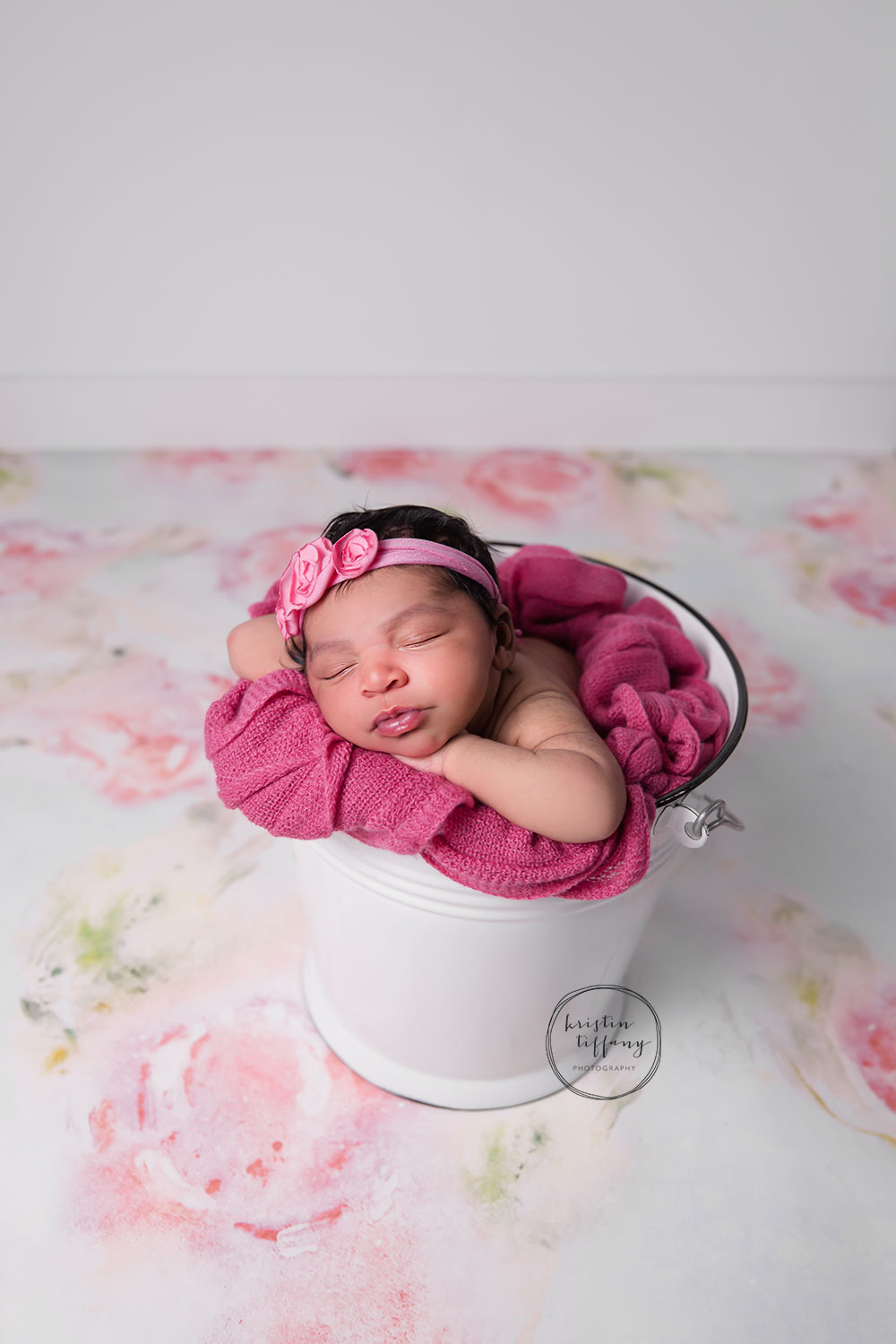 a newborn photo of a baby girl in a bucket with a pink headband