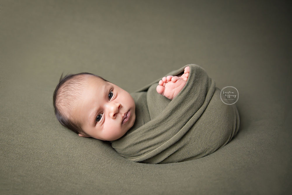 a photo of a baby boy wrapped in green fabric