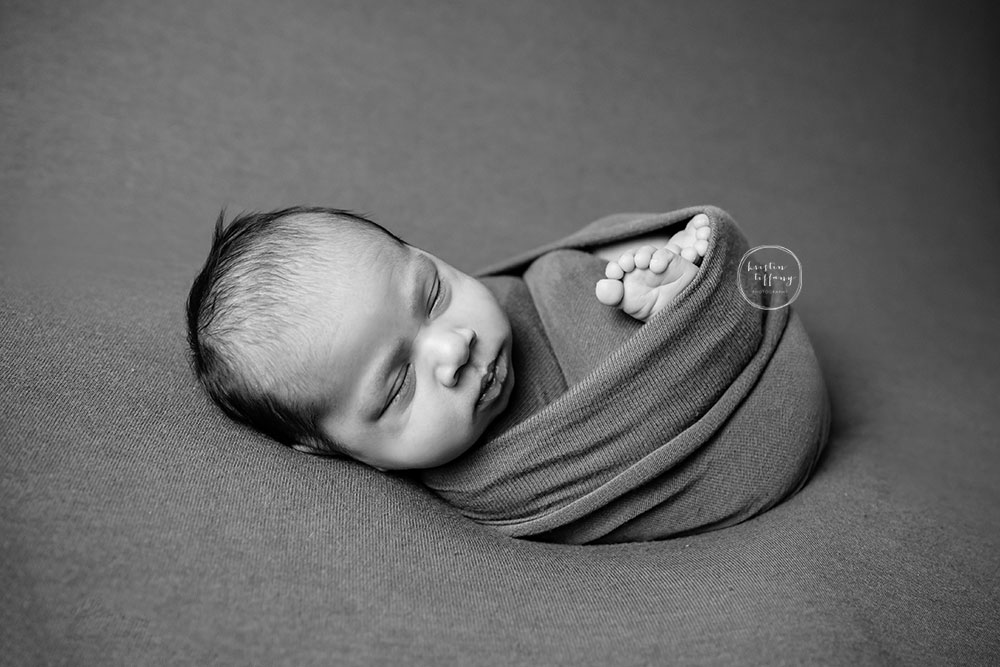 a black and white photo of a baby boy swaddled and asleep