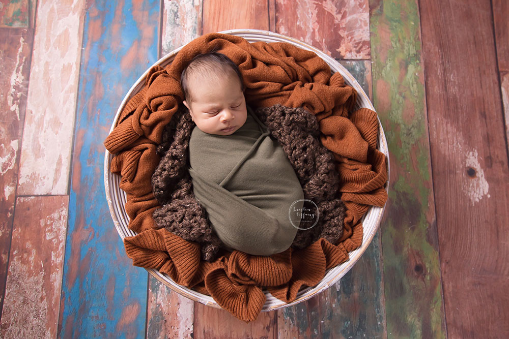 a photo of a baby sleeping in a bowl