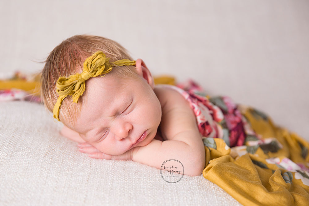 a photo of a baby girl in a yellow tieback and floral wrap