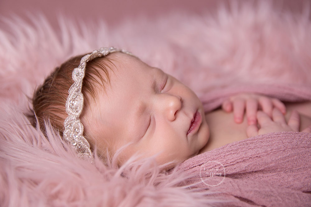 a photo of a sleeping newborn in faux pink fur