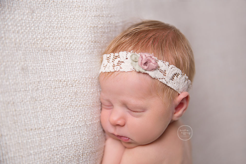 a photo of a newborn baby girl asleep at a newborn photo shoot