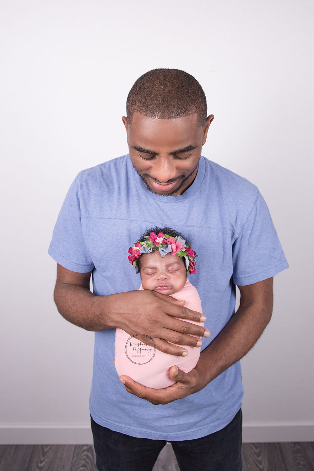 a photo of a newborn baby girl with her dad at a posed newborn session