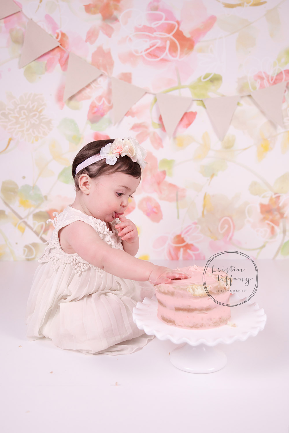 a photo of a baby girl eating cake at her cake smash session