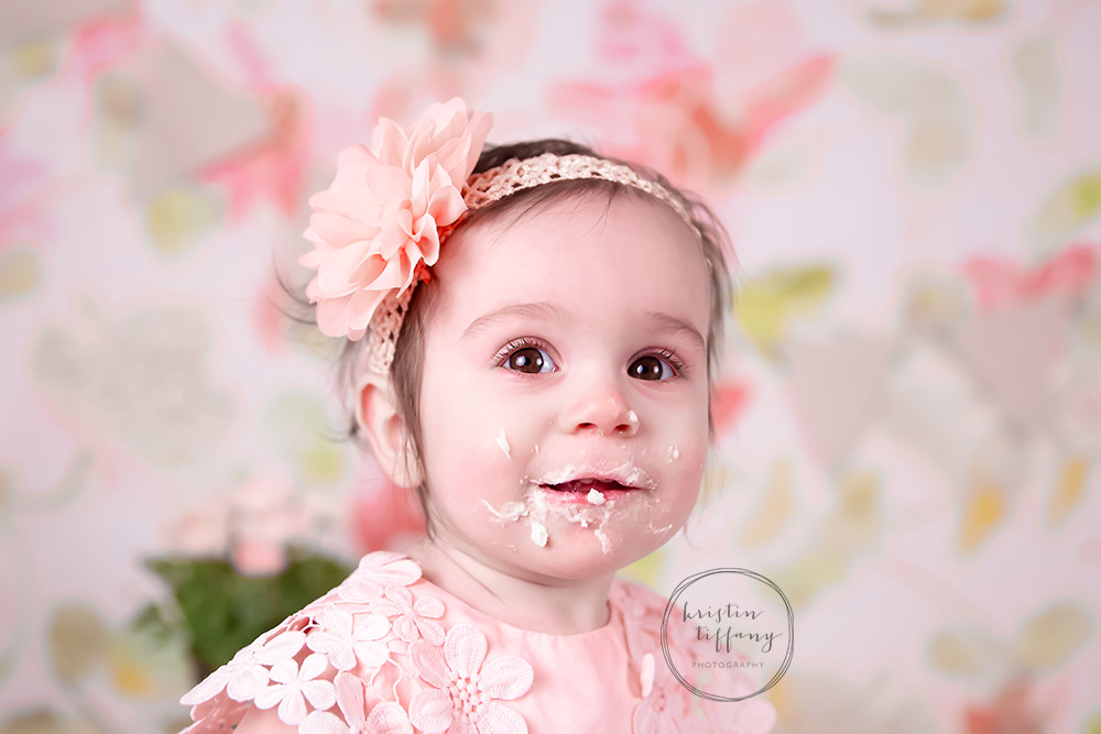 a photo of a baby girl with cake icing on her face
