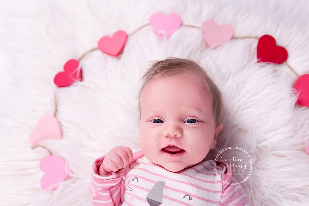 a photo of a baby girl smiling on a fur rug with hearts around her