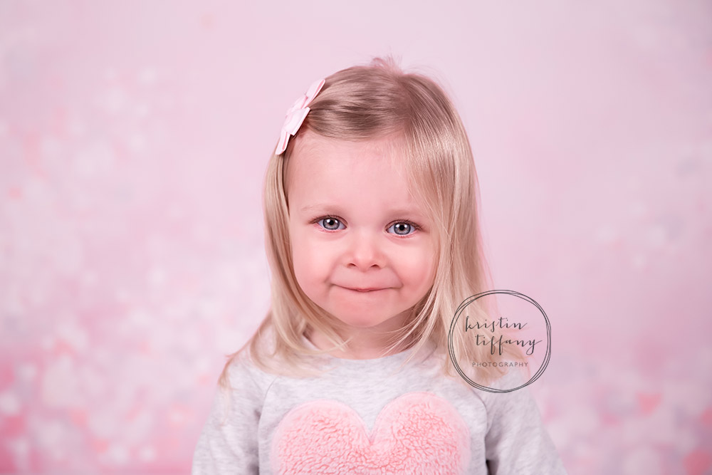 a photo of a little girl with a pink backdrop and heart shirt