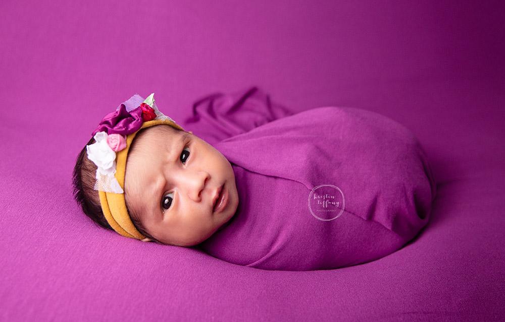 a newborn photo of a wide awake alert baby girl