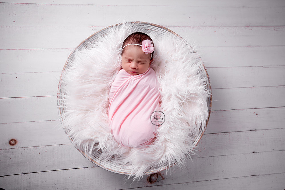 a newborn photo of a baby girl swaddled in a basket