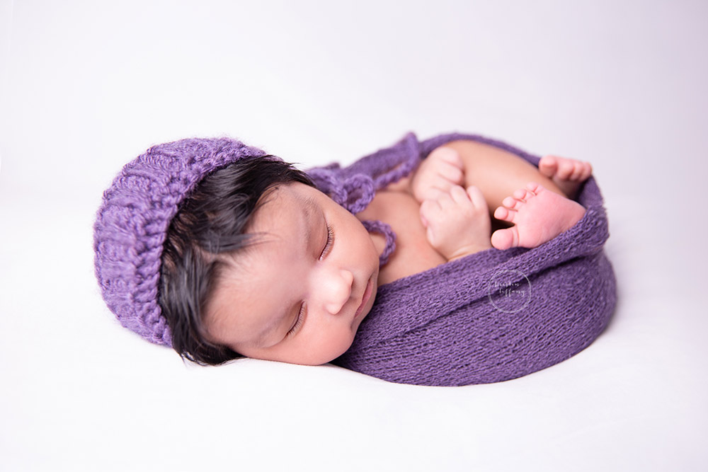 a photo of a baby girl swaddled in a purple wrap