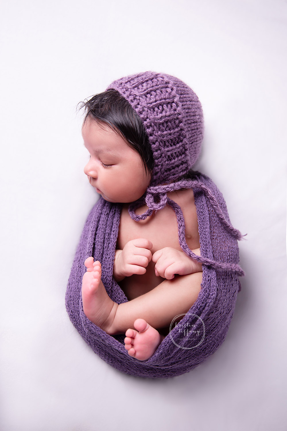 a newborn photo of a baby girl in purple