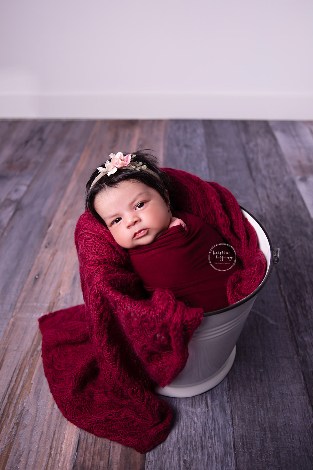 a newborn photo of a baby girl in a bucket