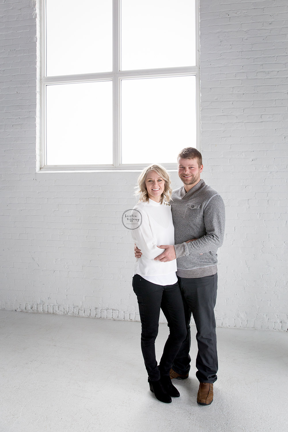 a photo of a couple in an all white studio