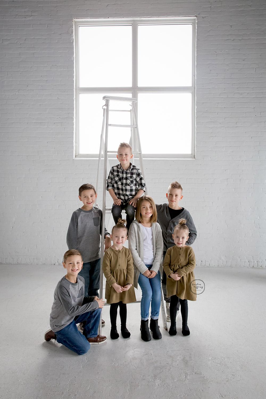 a photo of grandkids taken in an all white studio