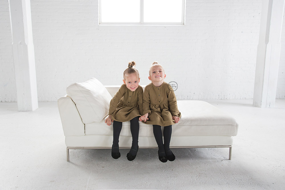 a photo of twin girls in an all white studio