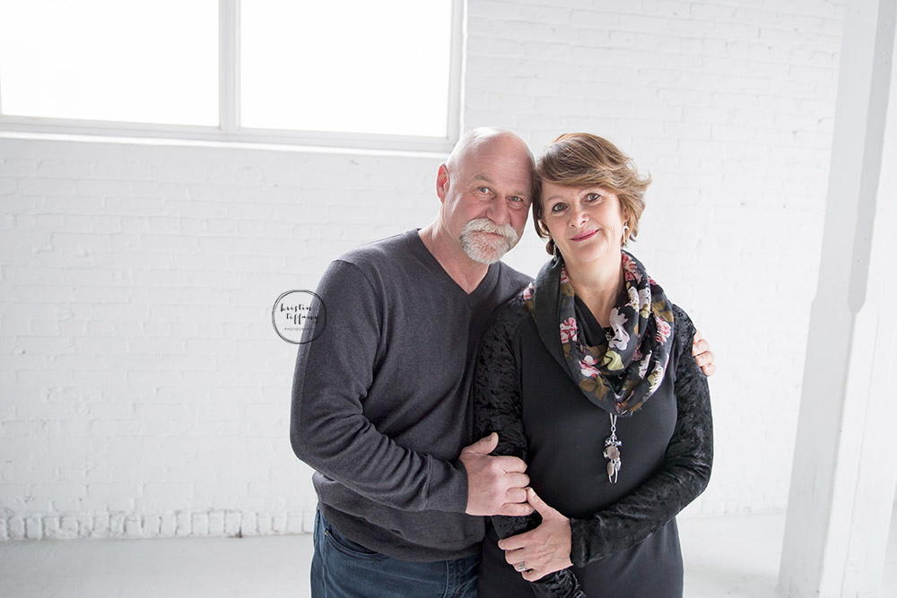 a photo of a husband and wife in an all white studio