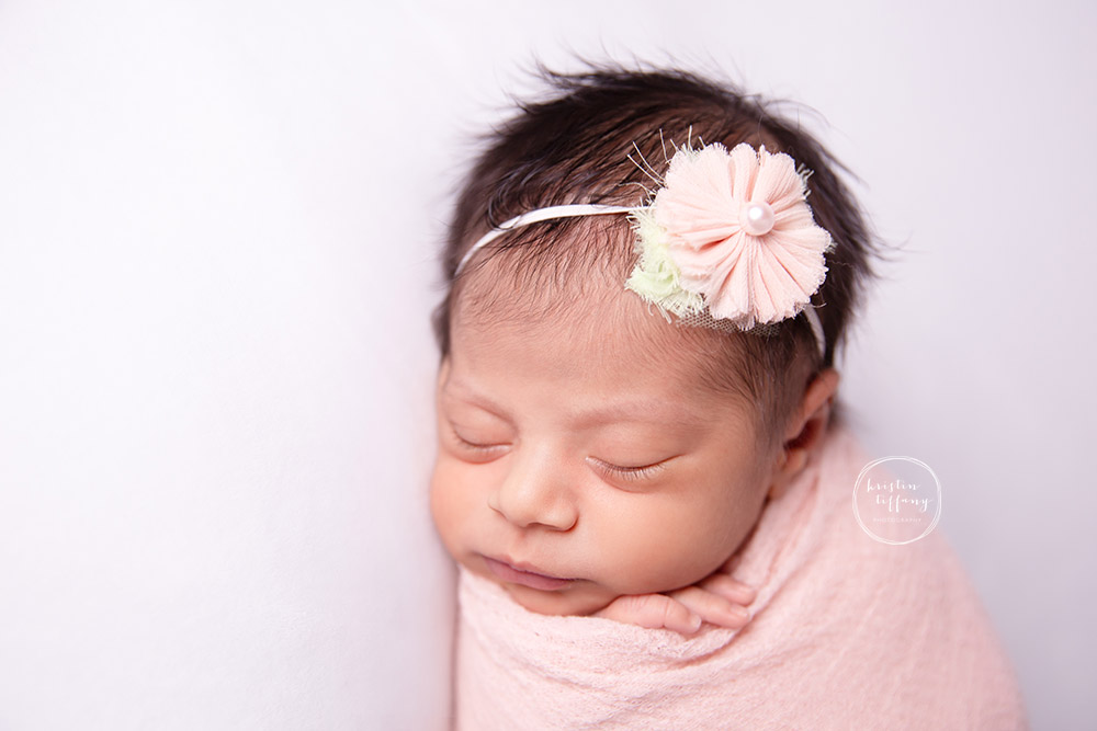a photo of a newborn baby girl sleeping in floral headband