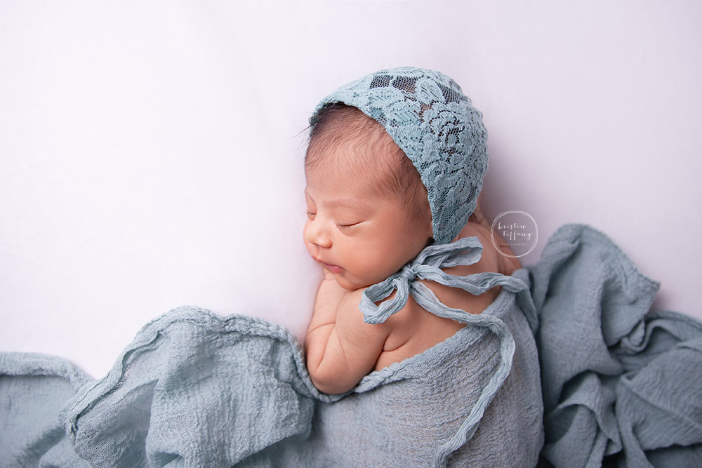 a newborn photo of a baby girl sleeping in a green lace bonnet and wrap