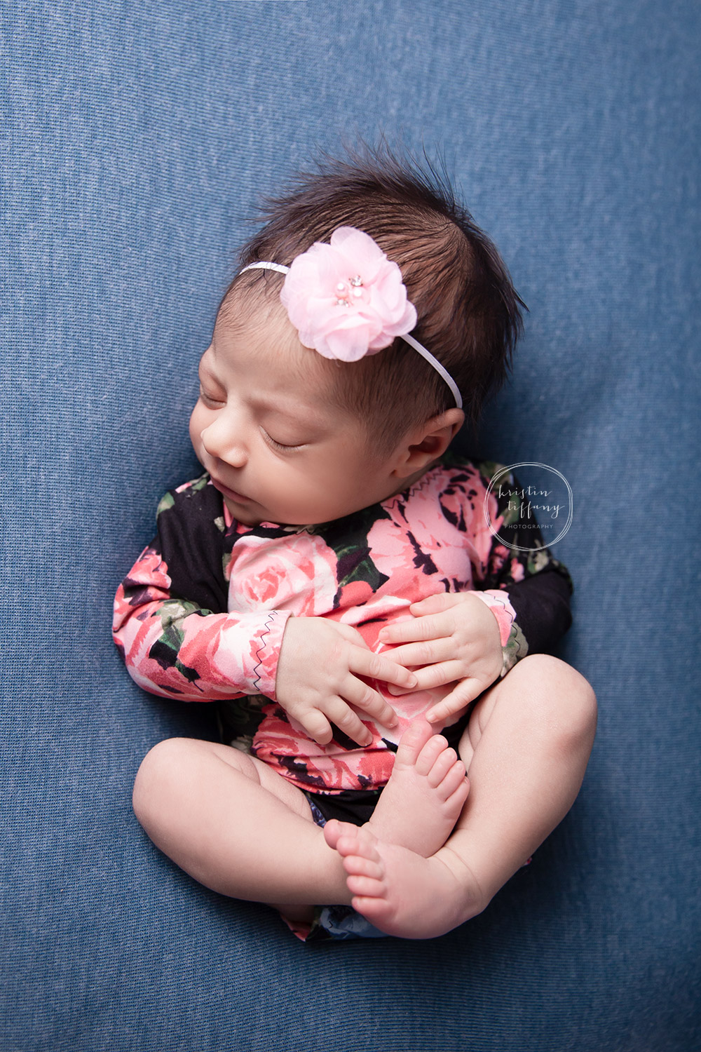 a newborn photo of a baby girl in a floral romper
