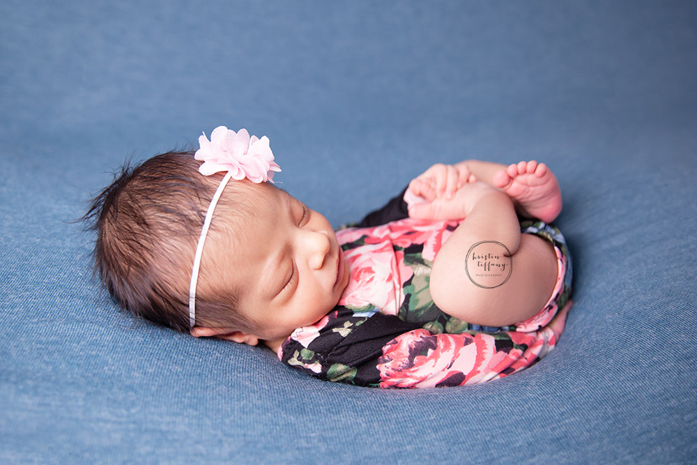 a newborn photo of a baby girl sleeping in a floral romper