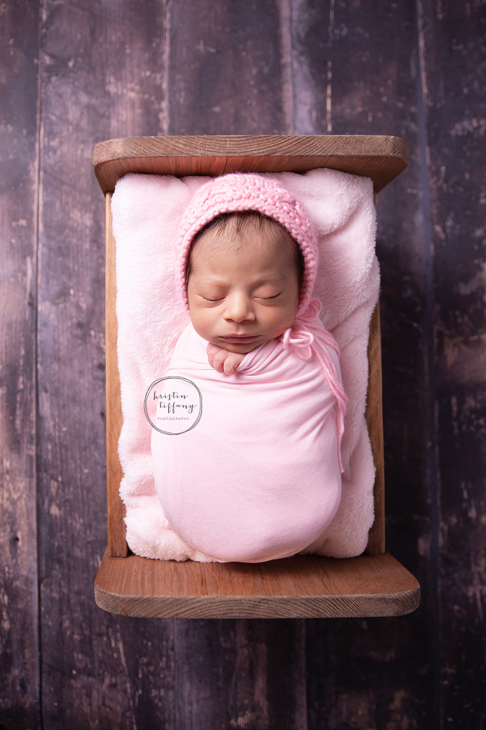 a photo of a newborn sleeping in a wooden bed