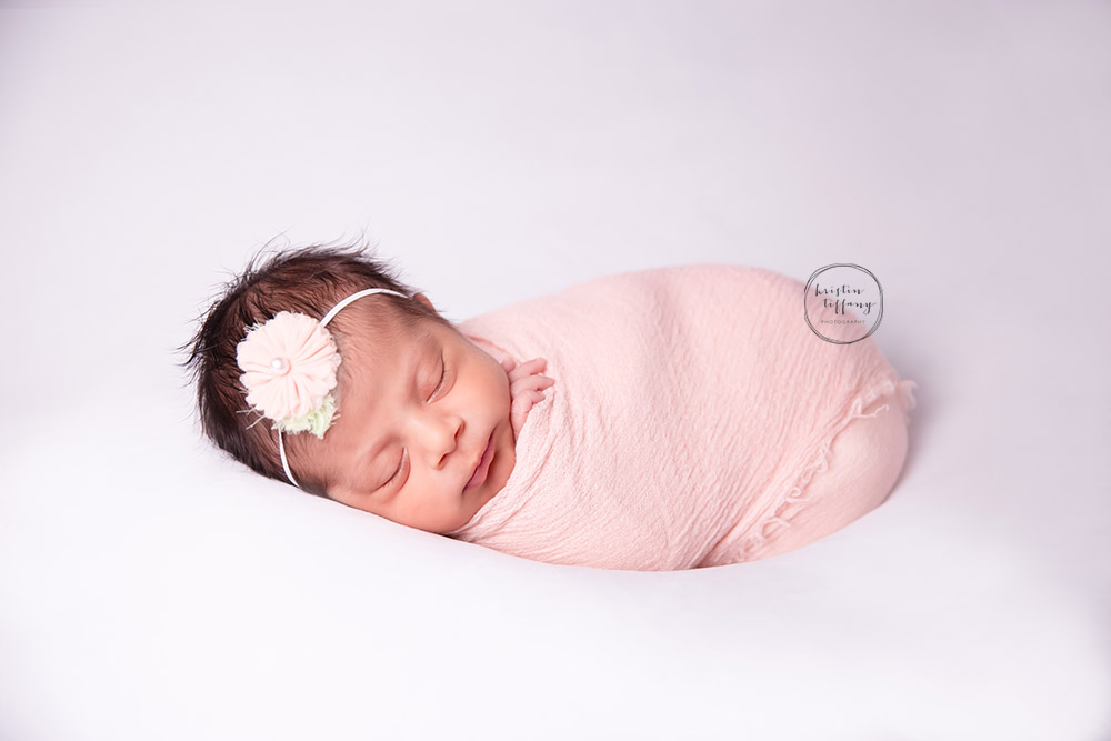 a newborn photo of a baby girl swaddled in a wrap
