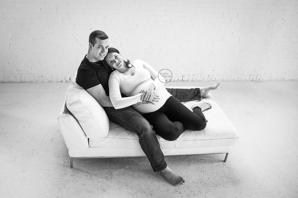 a maternity photo of a couple cuddling on a couch
