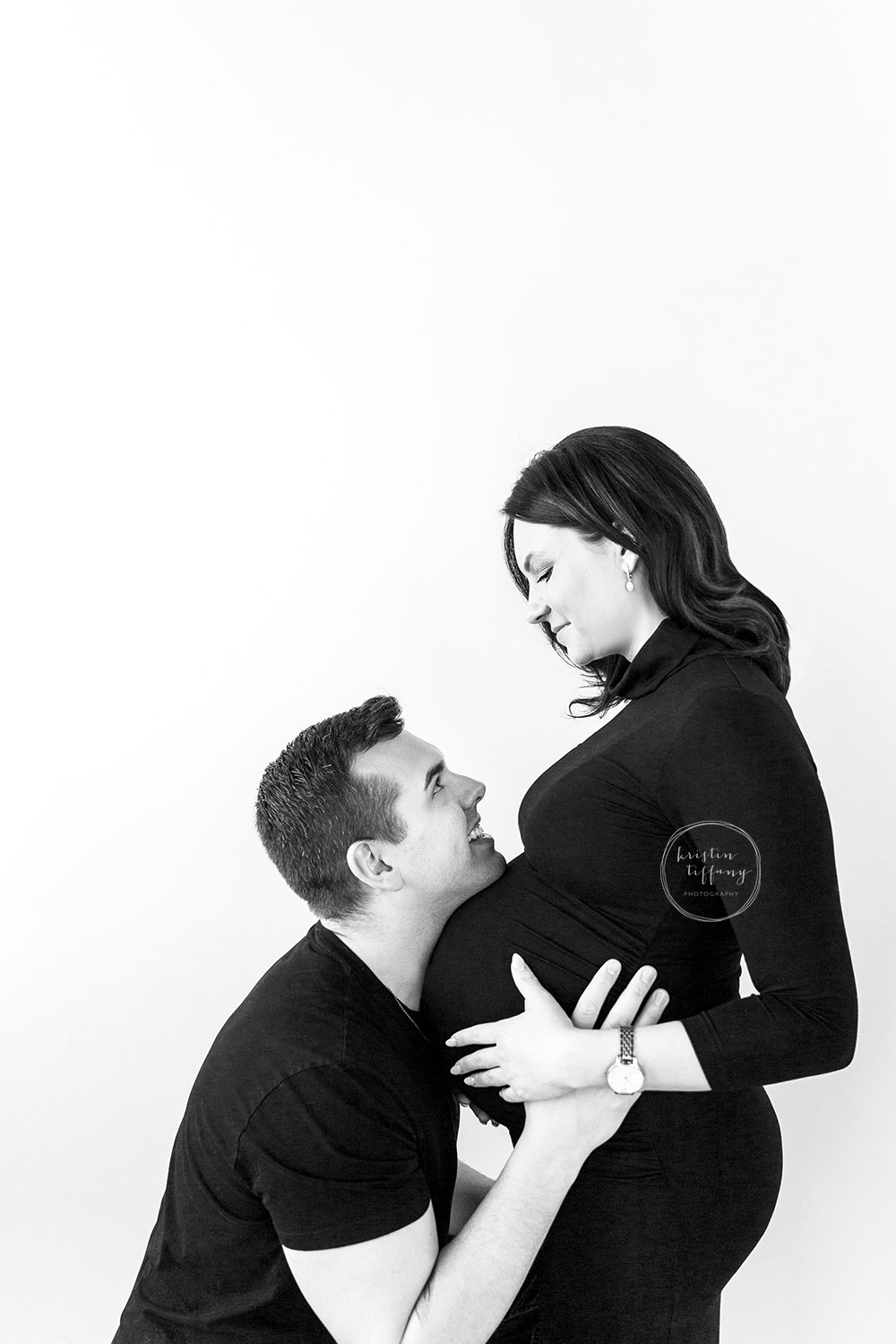 a maternity photo of a husband holding his wife's belly