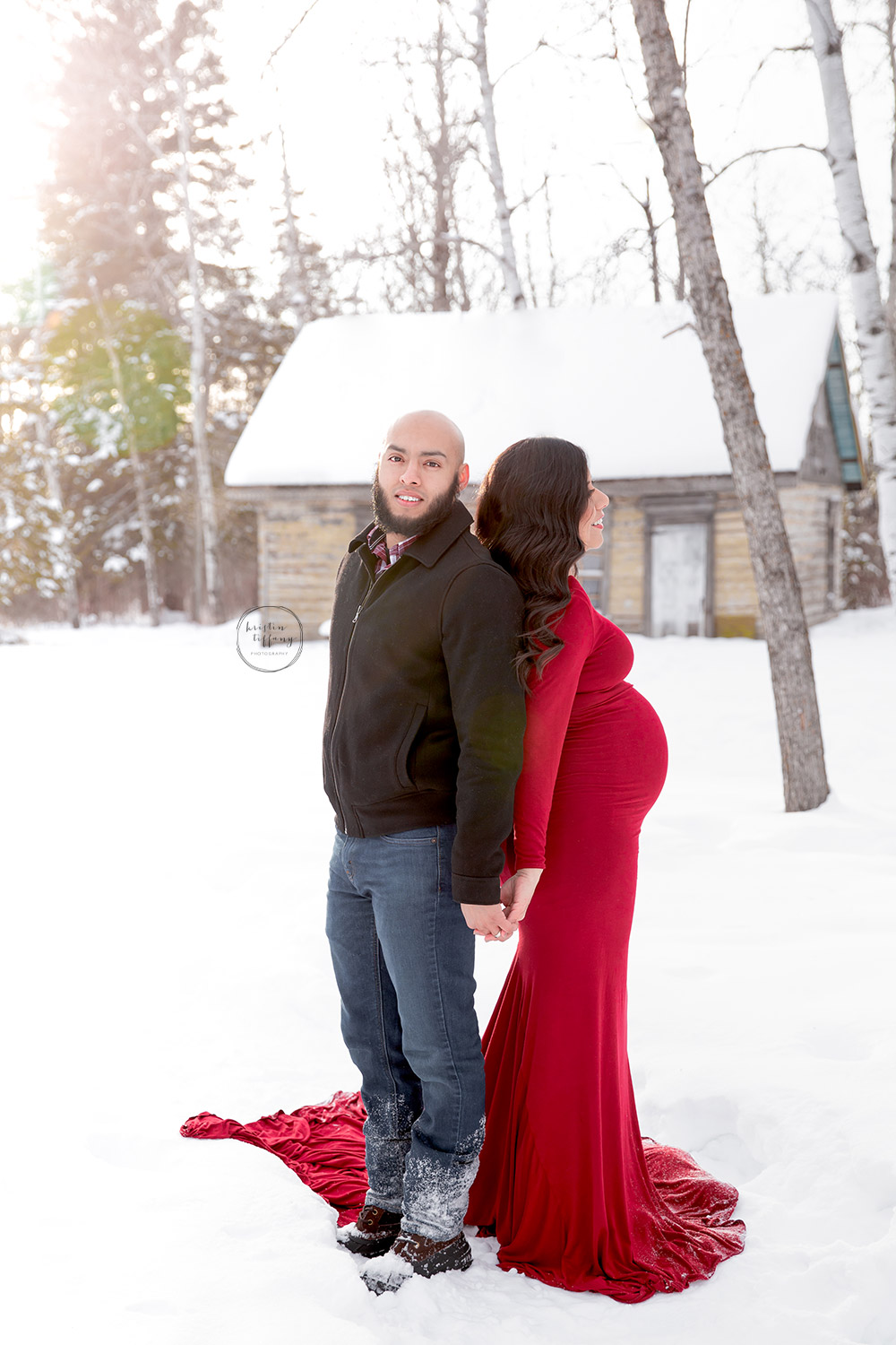 a maternity photo of a couple in the snow