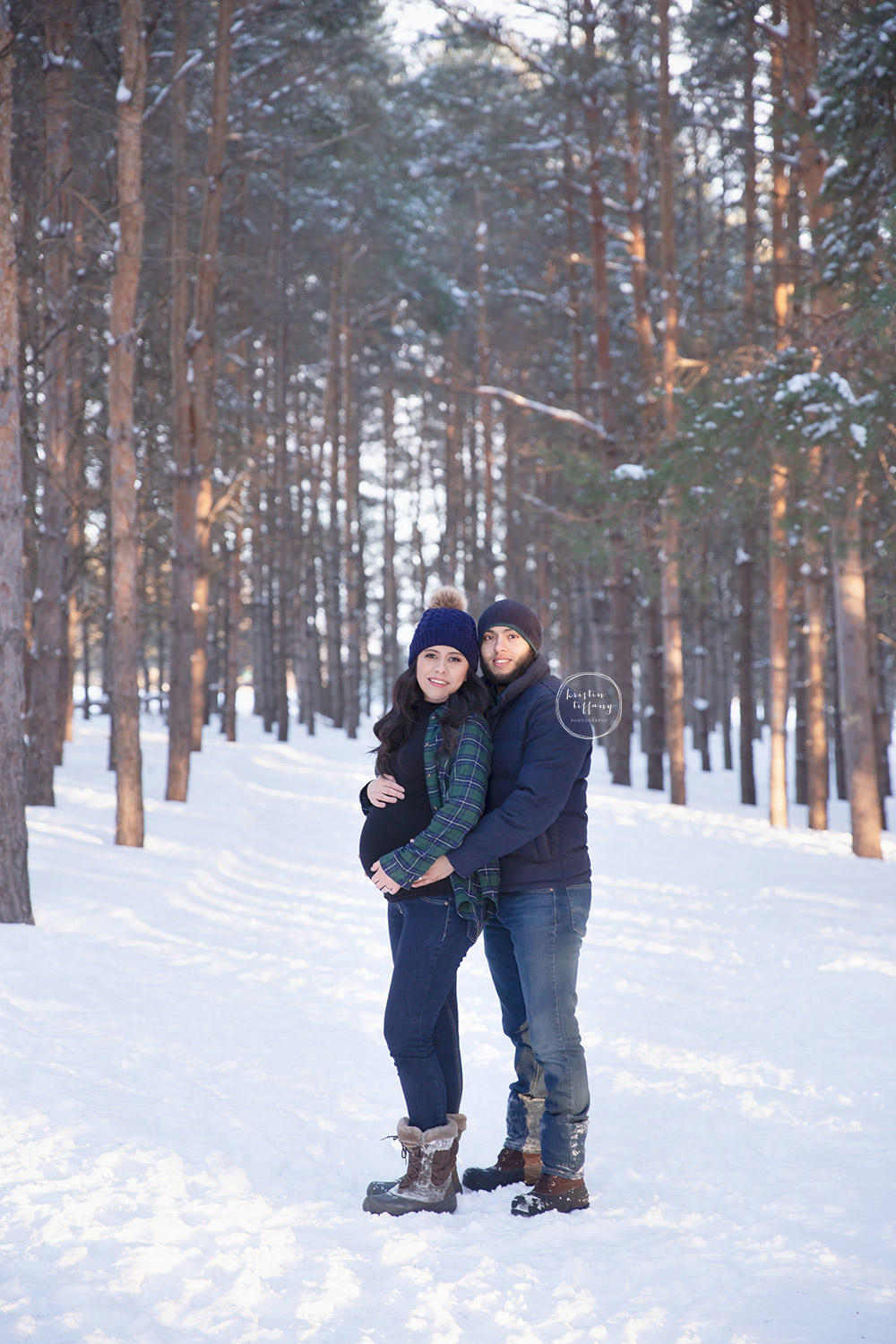 a maternity photo taken in the snowy woods