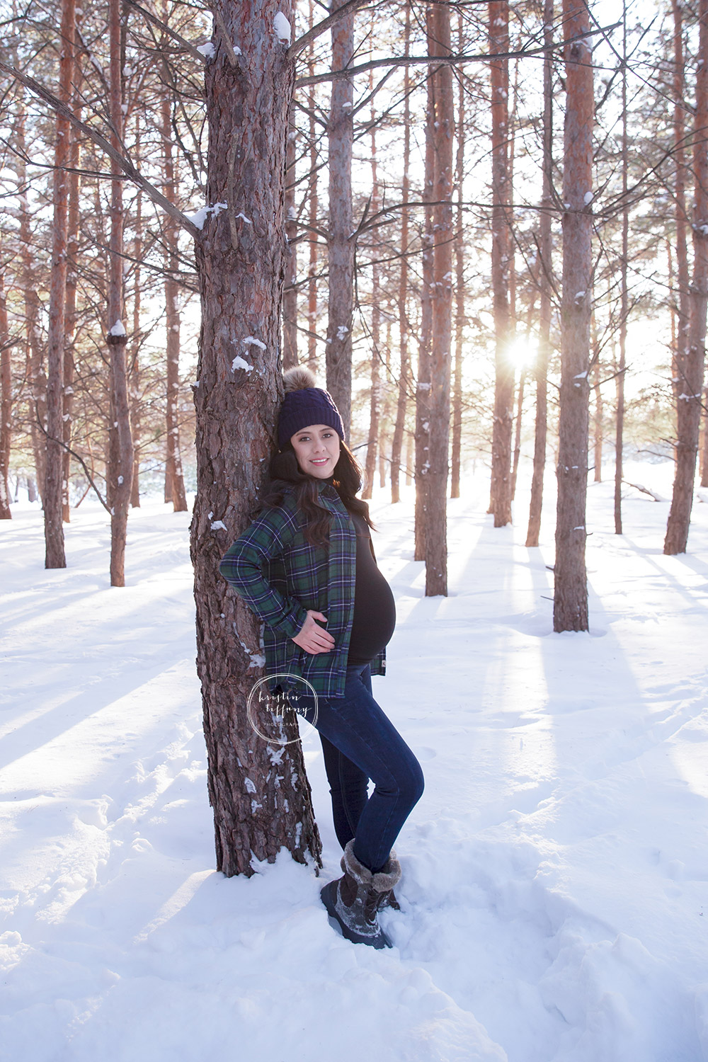 a maternity photo taken in the snow in the woods
