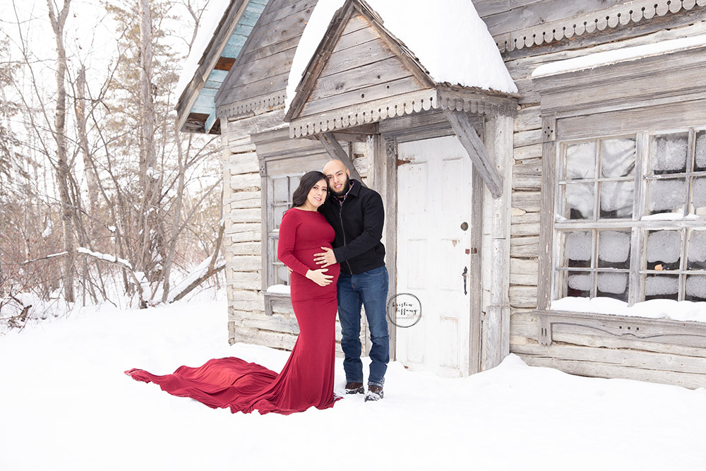 a maternity photo of a couple at an old homestead
