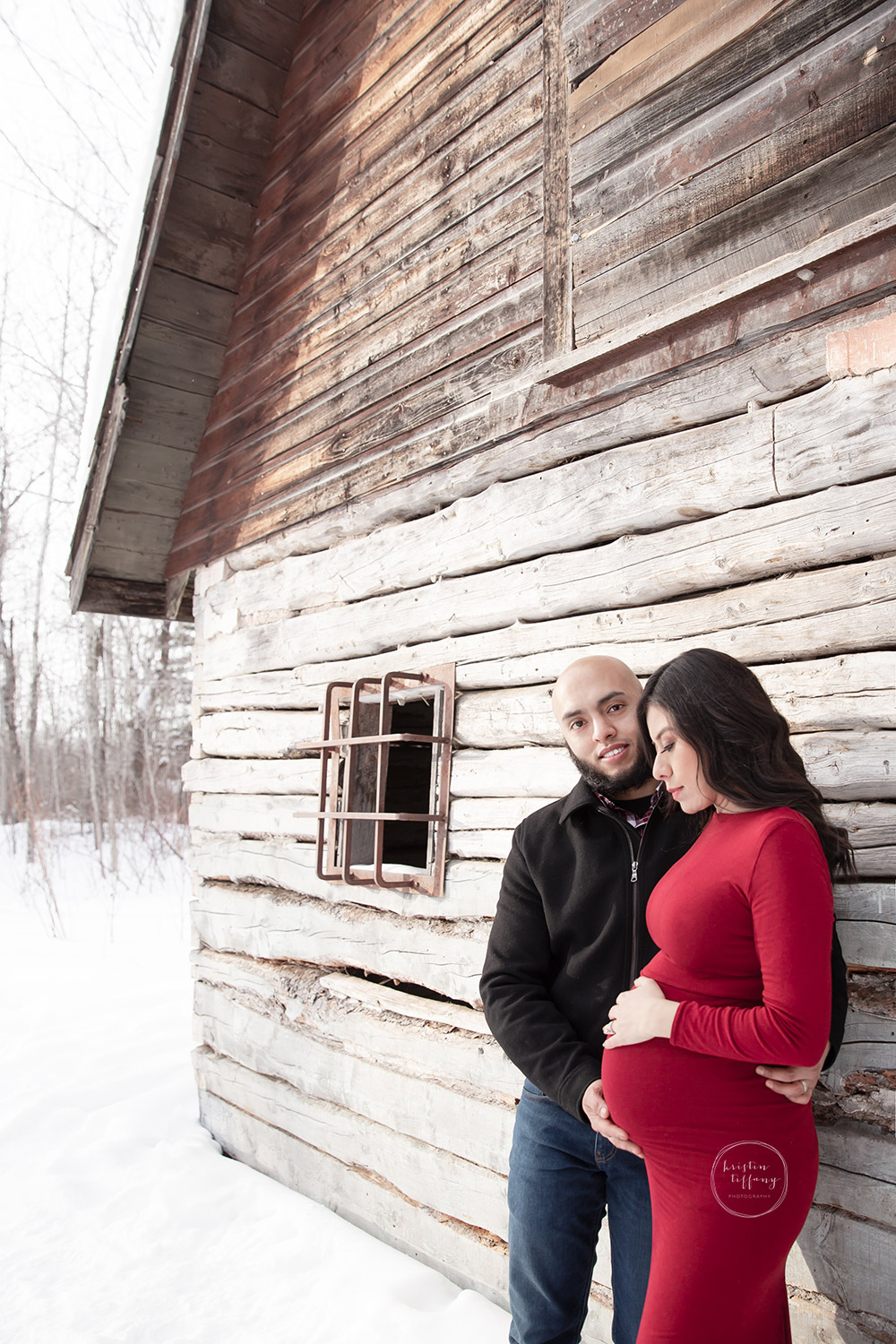 a maternity photo of a couple by an old wooden home