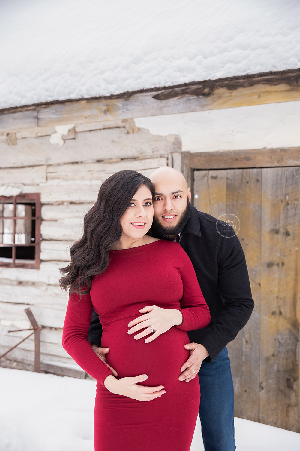 a maternity photo of a couple in front of an old home