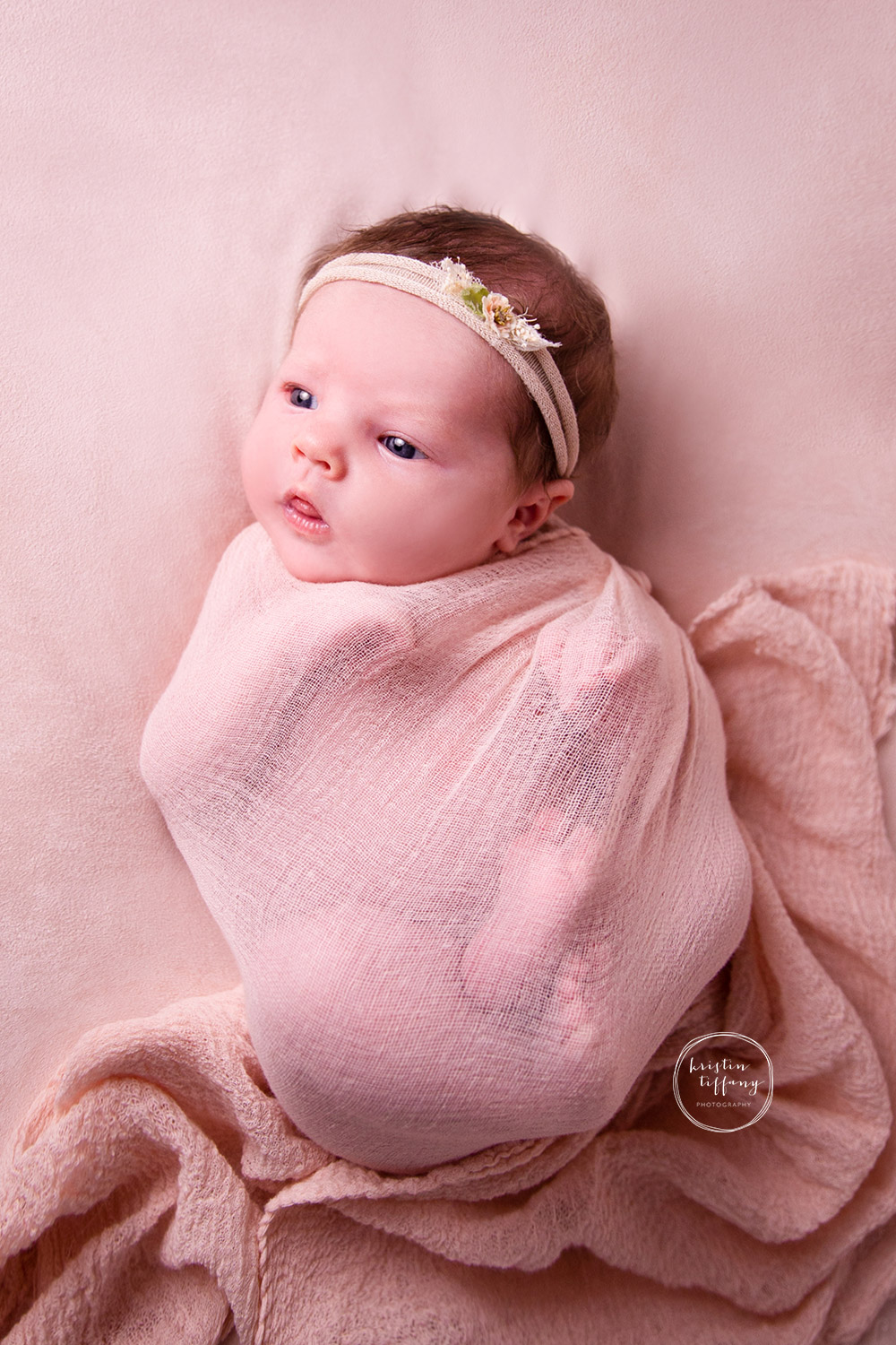 a photo of a newborn baby girl wrapped in a cheesecloth wrap