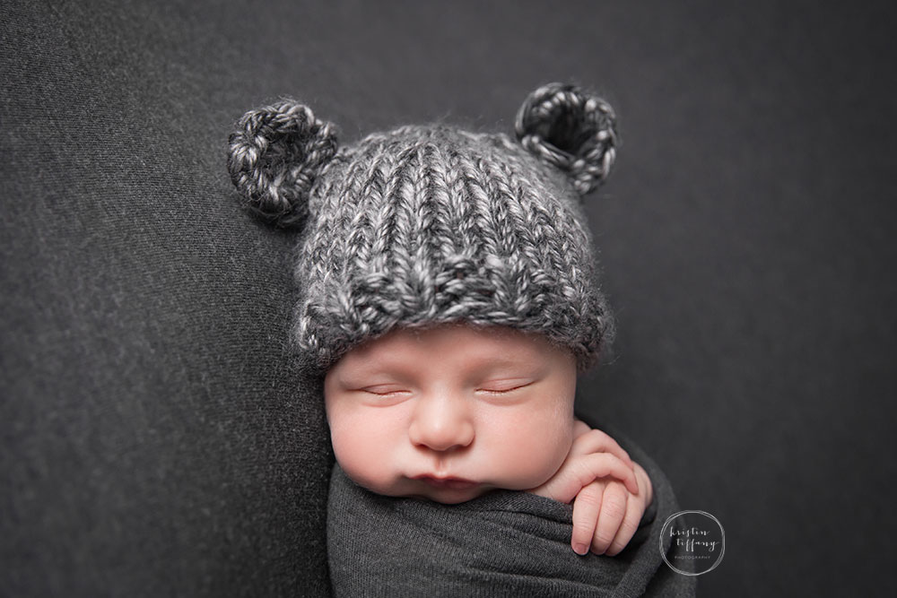 a posed newborn session of a baby boy in a bear hat