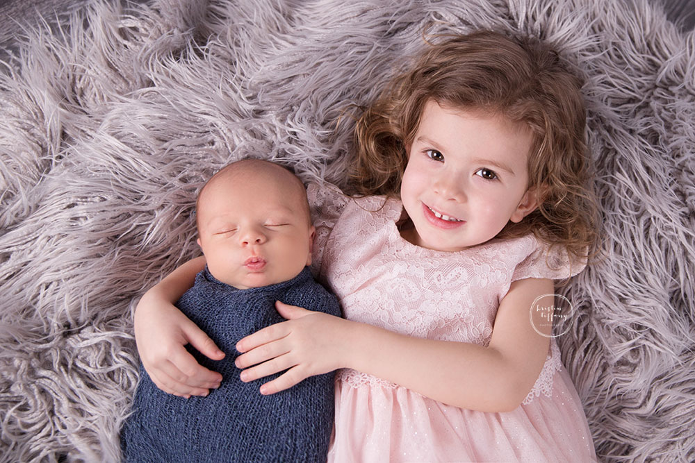 a posed newborn session of a baby boy and his big sister